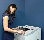 picture of blue-collar-worker  - A young Asian girl working at a busy office fax machine - JPG