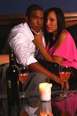 African American couple share a romantic candlelit glass of wine