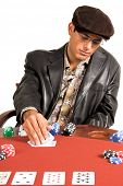 Hispanic man looking at his hole cards while playing Texas Hold um poker. Problem is he is wearing g