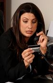 Business woman using a credit card to make a purchase over the phone