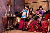 image of vaudeville  - Rabble rousing group of burlesque dolls dancers gathered on the bed of their dressing room - JPG