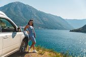 Woman Standing On Cliff Near White Suv Car With Beautiful View Of Sea Bay With Mountains. Road Trip poster