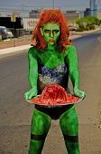 Sexy female zombie trudging down the street with a brain on a silver platter