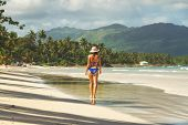 Traveler Girl Walking In Bikini On A Tropical Beach. Young Girl Traveler Walking In Nature. Traveler poster