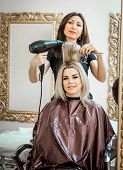Stylish Professional, Hairdresser Doing Hairdoing To The Client With A Hair Dryer On The Background  poster