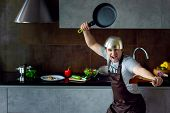Funny Loser Man Male Guy With Metal Sieve, Frying Pan, Wooden Kitchen Utensils And Apron Trying To C poster