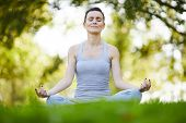 Content peaceful attractive young woman with closed eyes sitting in lotus position on grass and hold poster