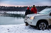 Couple Standing Near Suv At Riverside In Winter Time Enjoying The View. Snowed Landscape poster