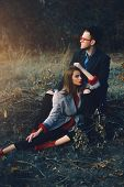Autumn fashion. Beautiful fashionable couple on yellowed autumn grass and leaves. poster