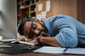 Tired multiethnic businessman sleeping in office. Middle eastern business man with eyeglasses worked poster