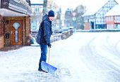 Man With Snow Shovel Cleans Sidewalks In Winter During Snowfall. Winter Time In Europe. Young Man In poster