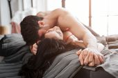 Passionate Sexy Young Couple Lying On Bed In Room. He Is Above And Kiss Model. Couple Hold Hand In H poster