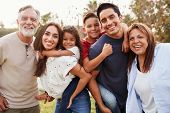 Three generation Hispanic family standing in the park, smiling to camera, selective focus poster