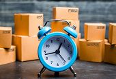 Cardboard Boxes And A Blue Alarm Clock. Time Of Delivery. Limited Supply, Shortage Of Goods In Stock poster