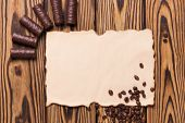 Row Of Yummy Chocolate Candies And Fried Halves Of Coffee Beans Near Blank Burnt Paper On Old Weathe poster