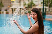 Young Beautiful Woman Making Water Splash In Sexy Bikini At The Pool.enjoying Summer.young Slim Fit  poster