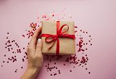 Gift Box Wrapped In Brown Colored Craft Paper And Tied With Red Bow On Pink Background With Red Conf poster