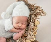 Cute little baby in white hat and knitted suit sweetly sleeping on furry brown pillow poster