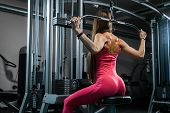 Athletic Woman Using Machine For Pumping Back Muscles In Gym, Back View. Woman Trainer Shows How To  poster