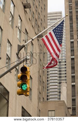 Skyscrapers, American Flag And Traffic Light Shows Green.