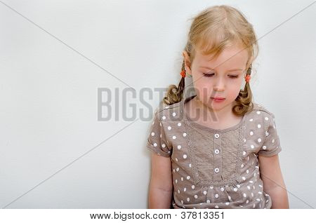 Portrait Of Sad Little Girl Standing Against The Wall. Space For Text