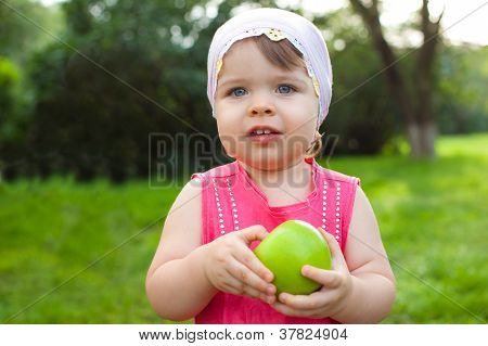 little girl holding green apple