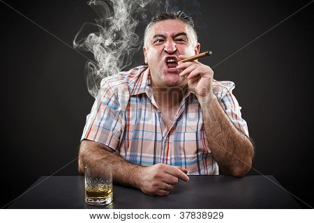 Mature Mafia Man Drinking And Smoking While Sitting At Table