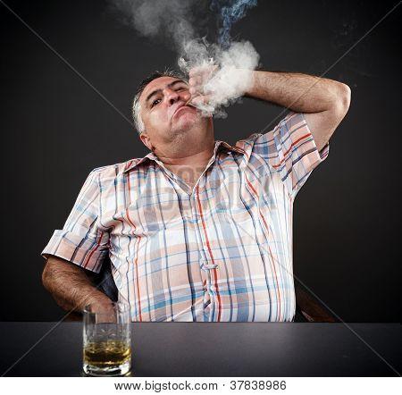 Mature Mafia Man Drinking And Smoking While Sitting At Table