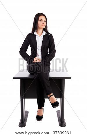 Young Businesswoman Sitting On Table Isolated On White