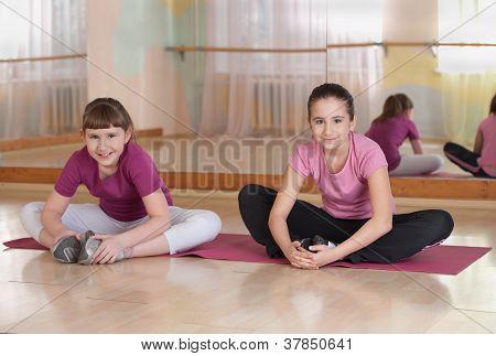 Two smiling girls engaged in physical trainingindoors.