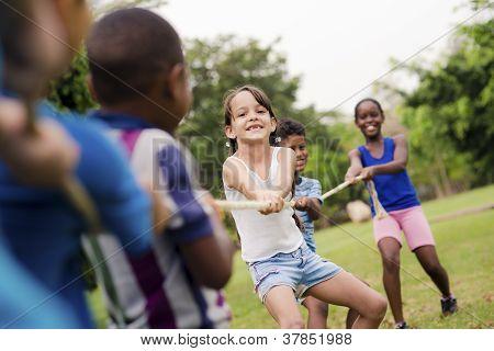 Escolares feliz jugando a tira y afloja con la cuerda en el Parque