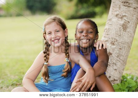 Two Happy Female Friends Hugging And Looking At Camera