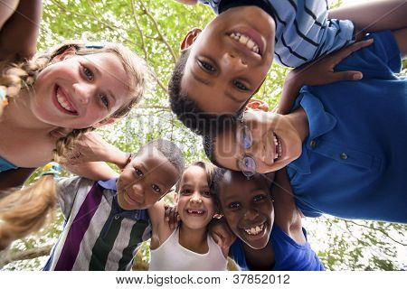 Children Embracing In Circle Around The Camera And Smiling