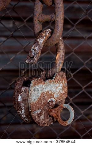 Old Padlock Hanging On A Chain