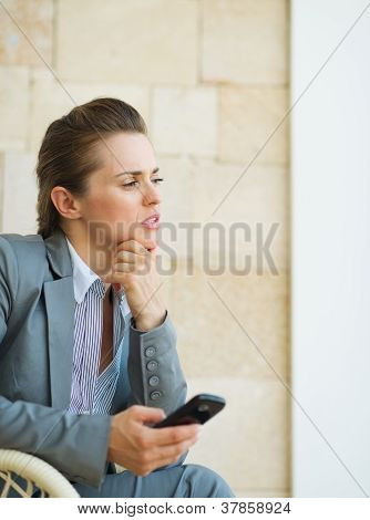 Concerned Business Woman Holding Mobile Phone