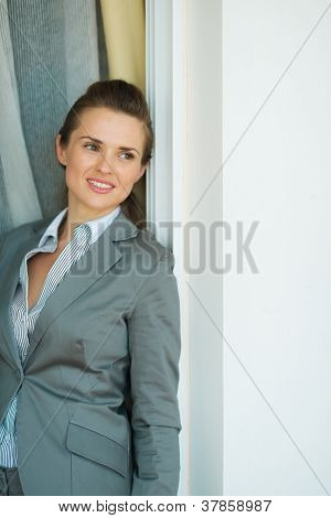 Portrait Of Thoughtful Business Woman Leaning On Jamb