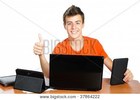 Excited Schoolboy Shows  Thumb Up While  Sitting At Table With Tablets And Laptop