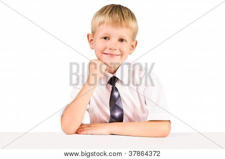 Portarat de sonreír elemental colegial mientras estaba sentado en una mesa aislada sobre blanco