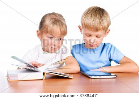 5-6 Years Old Girl Sitting At Table Using Digital Pad And Book Isolated Over White