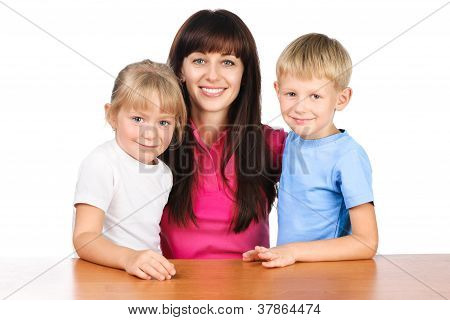Happy Mom Or Young Teacher Sitting At Table With Two Children Isolated Over White