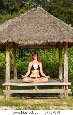 Woman Doing Yoga Meditation In Tropical Gazebo