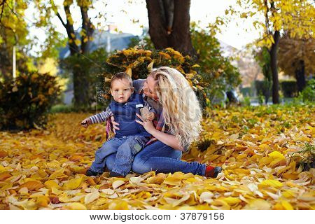 Attractive Curly Mother And Son Sitting On The Carpet Of Fallen Leaves In Autumn Park