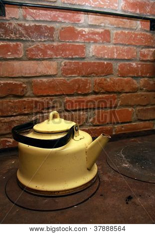 Yellow Tea Pot On A Stove, Red Brick Wall In Background