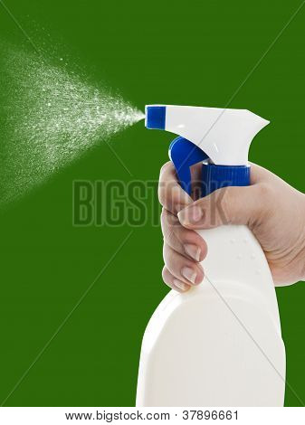 Hand With Cleaning Spray Bottle On Green