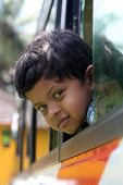 Handsome And Cute Little Indian School Kid Looking Back With Happiness From The Window Of A School B