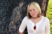 stock photo of young women  - Serious young blond standing in front of a large tree with a suspicious expression - JPG