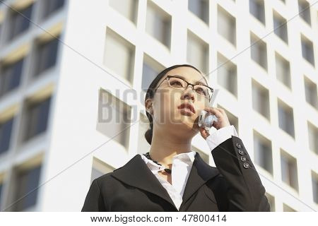 Low angle view of businesswoman with cell phone