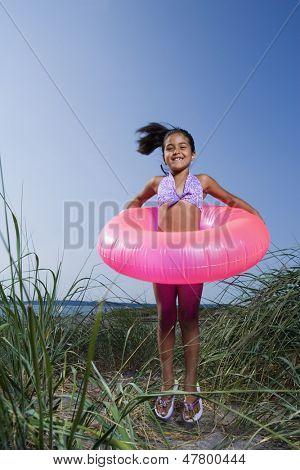 Little girl with inner tube on beach