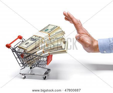 businessman's hand & shopping cart full of stacks of dollar bills - isolated on white background