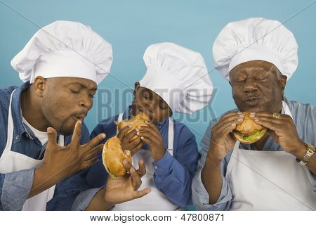 Male family members in chef's hats eating hamburgers